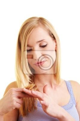 Blonde Frau betrachtet ihre Haarspitzen