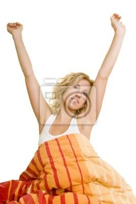 Blonde Frau sitzt im Bett und dehnt sich