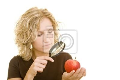 Blonde kobieta patrząc na czerwone jabłko z lupą