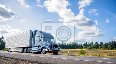Fototapeta Blue big rig semi truck with grille guard trabsporting frozen cargo in refrigerator semi trailer with skirt spoiler running on the straight road