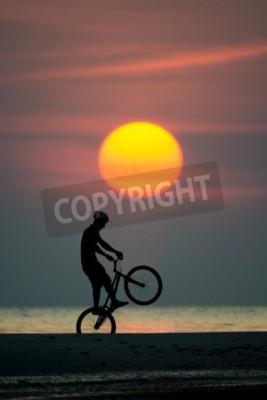 Fototapeta bmx działanie jeździec przeciwko zachód słońca na plaży.