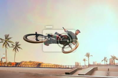 Fototapeta BMX rider is performing tricks in skatepark on sunset.