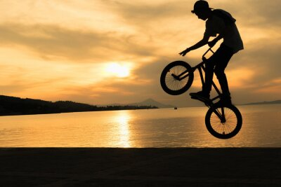 Fototapeta Bmx rowerzystę sztuczki przeciwko piękny zachód słońca.