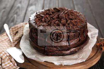 Fototapeta Board with delicious chocolate cake on wooden table