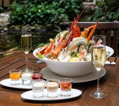 Fototapeta Bowl of gourmet fresh seafood on ice with savory sauce serve with white wine glass on vintage wooden table. Restaurant gastronomy food and drink consumerism concept.