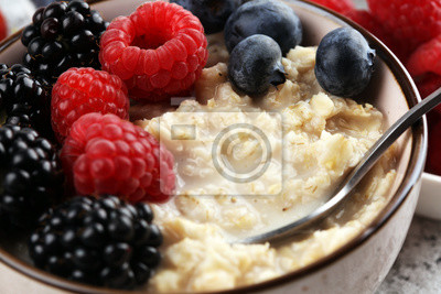 Bowl of oatmeal porridge with banana, raspberries coconut and caramel sauce on rustic table, hot and healthy food for Breakfast