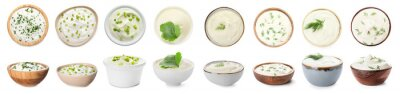 Fototapeta Bowls of tasty sour cream with herbs on white background