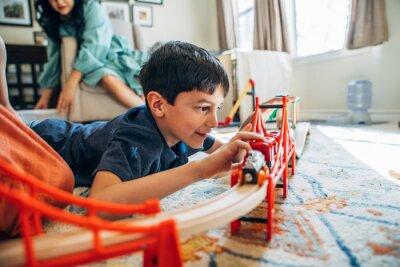 Fototapeta Boy playing with toy train in living room