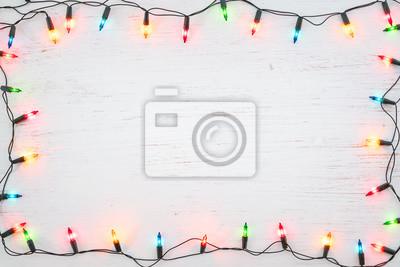 Fototapeta Bożonarodzeniowe światła żarówki ramy dekoracja na białym drewnie. Wesołych Świąt i nowego roku tło wakacje. widok z góry