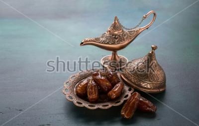 Fototapeta Brązowy talerz z datami i aladdin lampa na ciemnozielonym. Tło Ramadan. Ramadan Kareem.