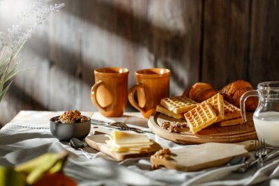 Breakfast on a wooden table in the light of the morning sun on a beautiful holiday day