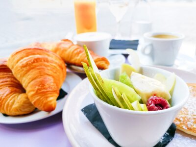 Breakfast with orange juice and fresh fruits on table