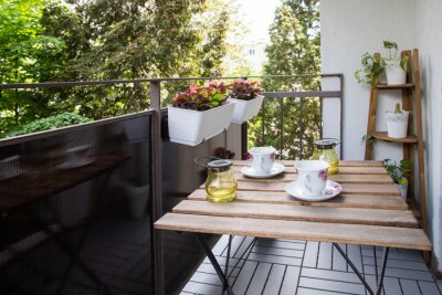 Fototapeta bright small apartment terrace in summer with flowers and coffee table