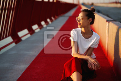 Fototapeta Bright summer lifestyle portrait of young pretty woman in eyewear, red skirt and white T-shirt, sitting on a bright red floor on the bridge.