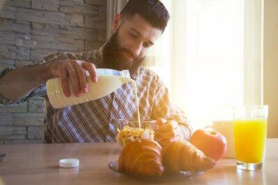 brodaty mężczyzna o śniadanie z płatki kukurydziane, mleko i bułki