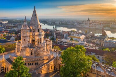 Fototapeta Budapest, Hungary - Beautiful golden summer sunrise with the tower of Fisherman's Bastion and green trees. Parliament of Hungary and River Danube at background. Blue sky.