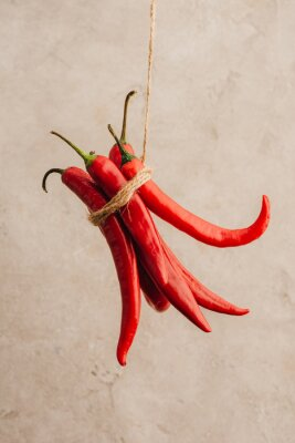 Fototapeta bunch of red chili peppers tied with rope hanging on beige concrete background