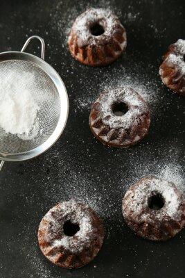 Fototapeta Bundt czekoladowe ciastka z cukrem pudrem na czarnym tle