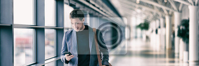 Fototapeta Business man texting on mobile phone at airport on business trip using cellphone texting sms message on smartphone app - young businessman commuter lifestyle panoramic banner.