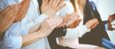 Fototapeta Business people clapping and applause at meeting or conference, close-up of hands. Group of unknown businessmen and women in modern white office. Success teamwork or corporate coaching concept