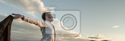 Fototapeta Businessman embracing life standing under cloudy sky