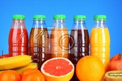 butelki soku z dojrzałych owoców na niebieskim tle