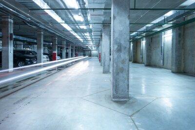 Fototapeta Car lights in the big underground city parking.