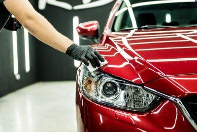 Fototapeta Car service worker applying nano coating on a car detail.