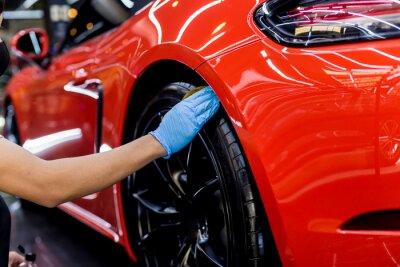 Fototapeta Car service worker polishing car wheels with microfiber cloth.