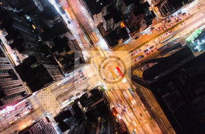 Fototapeta Car, taxi, and bus traffic on road intersection at night in Hong Kong downtown district, drone aerial top view. Street commuter, Asia city life, or public transportation concept