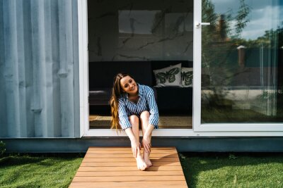 Fototapeta carefree beautiful female sitting in front of modern tiny house