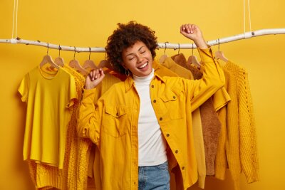 Fototapeta Carefree curly woman clothes buyer dances with happiness, raises arms, buys yellow clothing from new collection, rejoicing successful shopping day, being in high spirit, dances against outfits on rack