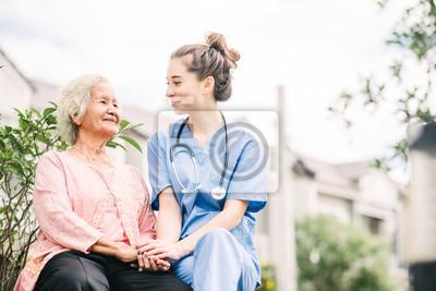 Fototapeta caregiver holding hand of happy elderly woman