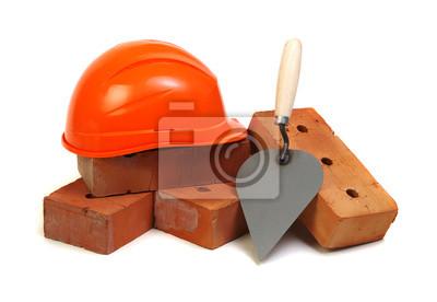 Cegła, czerwony twardy kapelusz i narzędzia