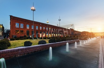 Fototapeta Centrum handlowe w Łodzi przekształcone z budynków przemysłowych do eleganckiego miejsca na zakupy na zachodzie słońca, Polska