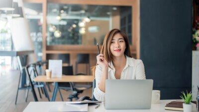 Fototapeta Charming asian businesswoman sitting working on laptop in office.