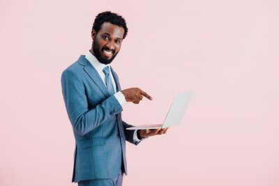 Fototapeta cheerful african american businessman pointing at laptop isolated on pink