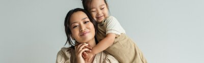Fototapeta cheerful asian toddler daughter hugging happy mother isolated on gray, banner