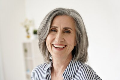 Fototapeta Cheerful satisfied 50s mature woman laughing looking at camera at home. Happy sophisticated classy mid age older gray-haired lady with white teeth dental smile posing for close up headshot portrait.