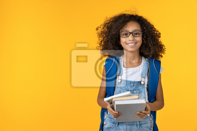Fototapeta Cheerful young african girl kid in eyeglasses holding notebook and books for study isolated over yellow background