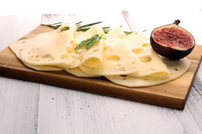 cheese slices on wooden tray with parsley. gauda cheese