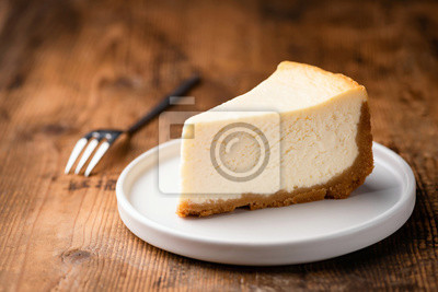 Fototapeta Cheesecake slice, New York style classical cheese cake on wooden background. Slice of tasty cake on white plate served with dessert fork