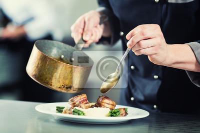Fototapeta Chef wlewając sos na naczynia w kuchni restauracji