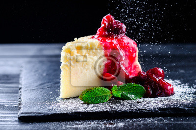 Fototapeta cherry cheesecake on a black background with reflection and flying icing sugar