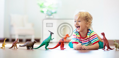 Fototapeta Child playing with toy dinosaurs. Kids toys.