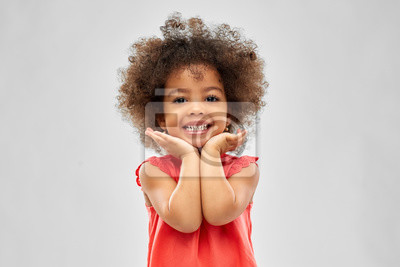 Fototapeta childhood and people concept - happy little african american girl over grey background