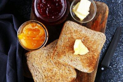 Chleb tostowy z domowym dżemem truskawkowym i pomarańczową marmoladą na rustykalnym stole z masłem na śniadanie lub brunch