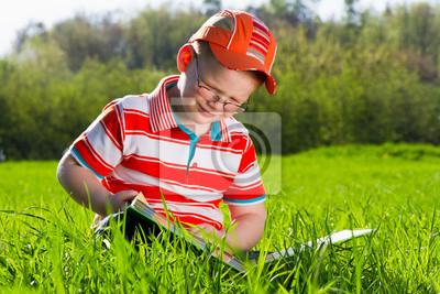 Chłopiec czyta książkę w parku na świeżym powietrzu