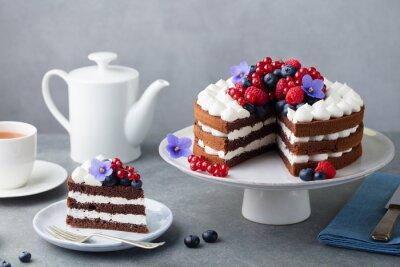 Fototapeta Chocolate cake with whipped cream and fresh berries. Grey stone background.