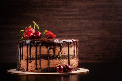 Fototapeta Chocolate cake with with berries, strawberries and cherries. cake on a dark brown background. copy space